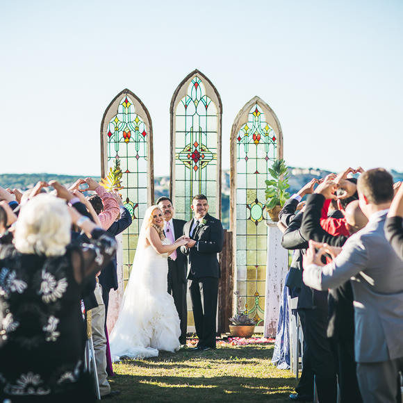couple getting married standing in front of a stained glass altar