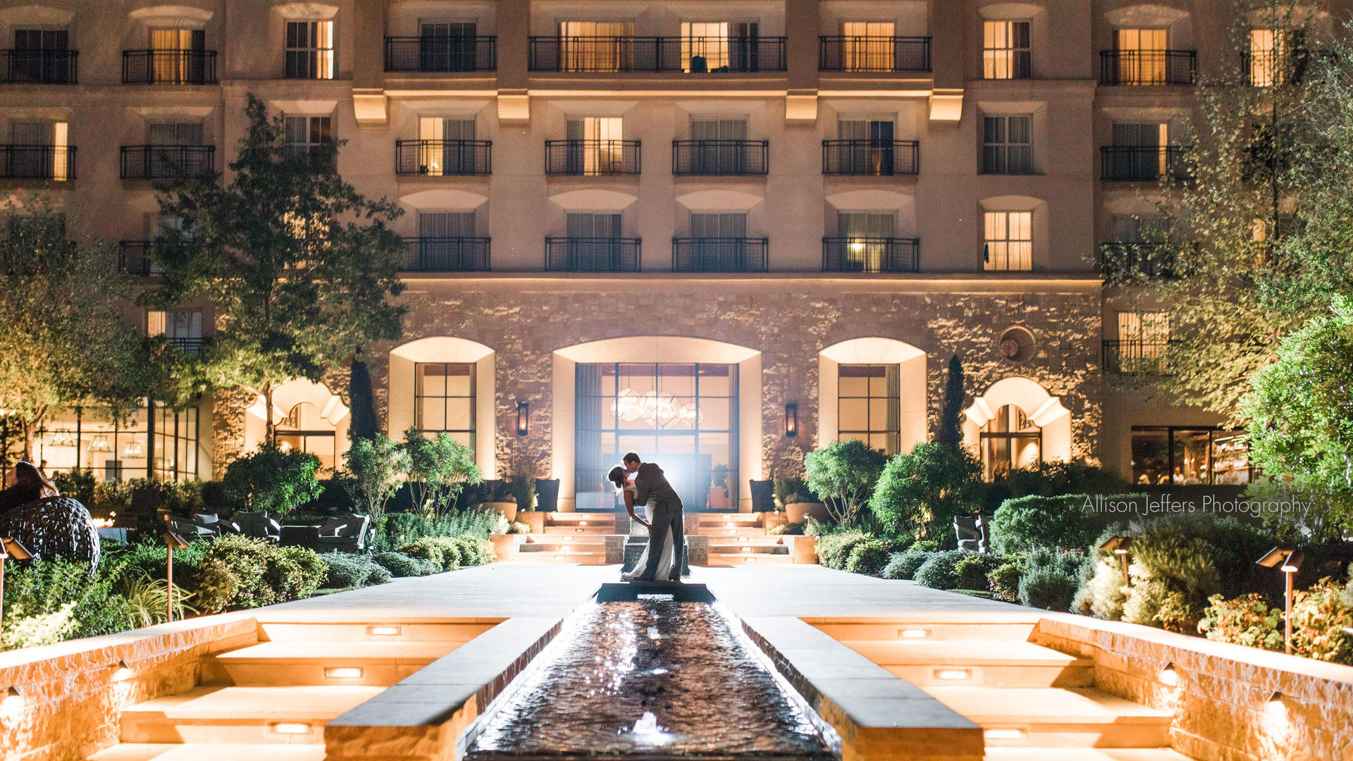 bride and groom kissing in front of la cantera resort