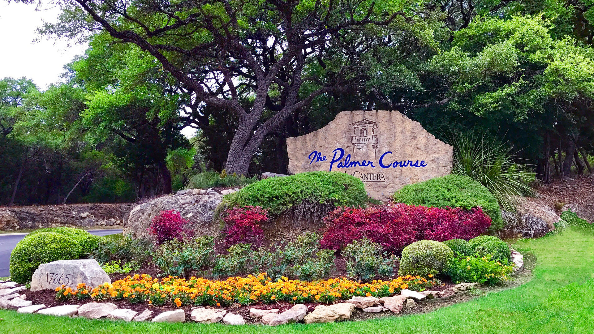 the palmer course entrance with rock and flowers