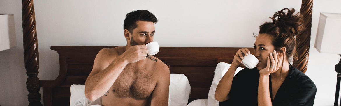 man and woman sitting in bed drinking coffee