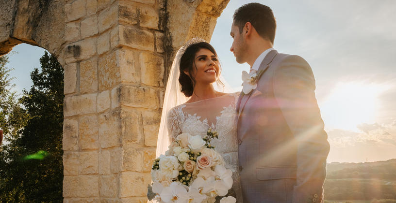 a bride and groom with sun in the background
