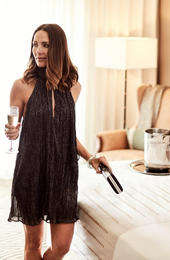 woman holding champagne next to her bed