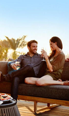 man and woman sitting on couch drinking wine