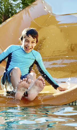 kid sliding down a water slide