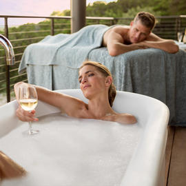 man receiving a massage and a woman in bathtub