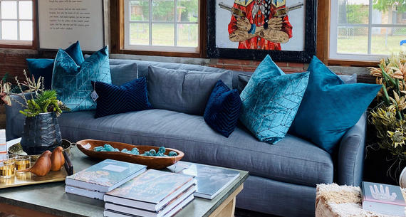 blue couch against a brick wall