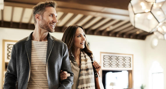 man and woman checking into hotel in fall