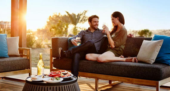 man and woman sitting on a couch outside drinking wine and smiling