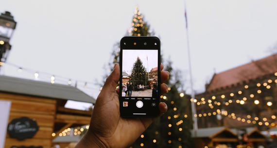 smart phone taking picture of couple in front of christmas tree
