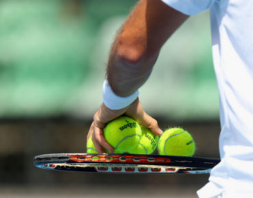 person holding pile of tennis balls on racket
