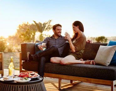 couple sitting on couch on patio drinking wine