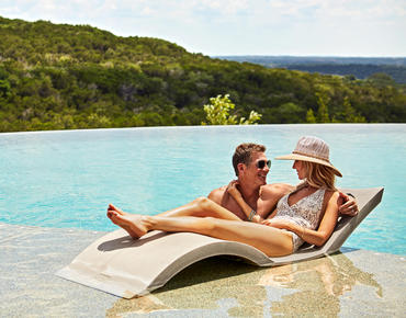couple sitting in infinity edge pool