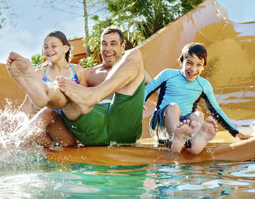 dad and two kids sliding down water slide
