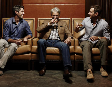 three men sitting in chairs having a drink