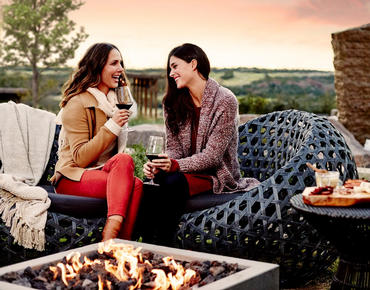 two women drinking wine by fire