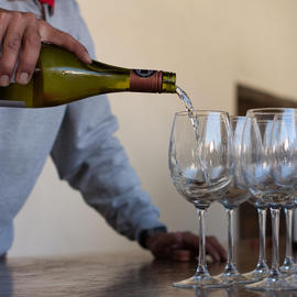 person pouring white wine into row of glasses