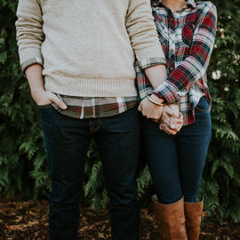 couple wearing plaid holding hands in front of green bushes