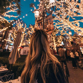 woman looking up at christmas lights in the street