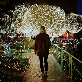 girl walking in botanical garden with lights